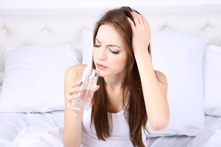 Девушка пьёт содовый раствор при болях в голове