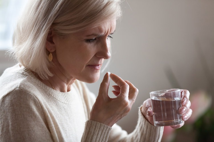 Женщина в возрасте принимает таблетку от мигрени